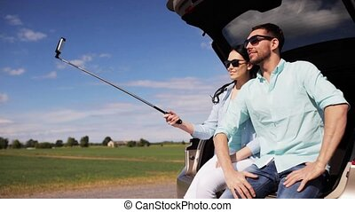 couple with smartphone selfie stick at car trunk 30 -...
