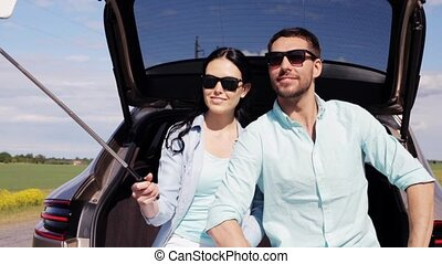 couple with smartphone selfie stick at car trunk -...
