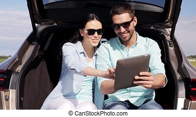 happy couple with tablet pc at hatchback car trunk 7 -...
