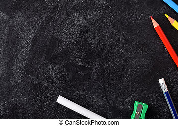 School supplies on the right side on a blackboard with chalk...