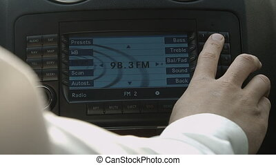 Mman switch the car radio - Human driving car and pushing...