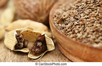 Cardamom seeds with other spices on wooden surface