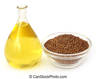 Ajwain seeds in a glass bowl with essential oil over white...