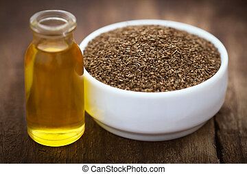 Ajwain seeds in a bowl with essential oil on wooden surface