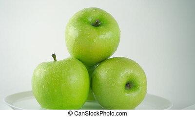 Girl hand taking one wet green apple, light background. 4K...