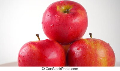 Red apples and dripping water, light background. 4K ProRes close up dolly shot