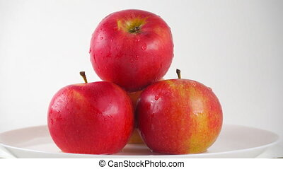Red apples on plate and dripping water against white background. 4K ProRes dolly shot