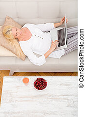 Woman with laptop and cherry on the sofa - A mature woman...
