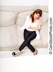 A beautiful mature woman talking on her cell phone on the...
