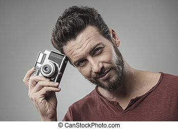 Confident man holding a vintage camera - Confident smiling...