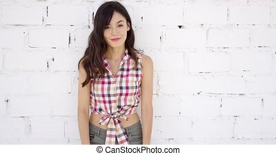 Attractive woman with checkered top and shorts stands...
