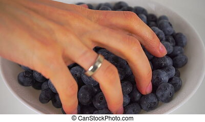 Female hand scooping blueberries from white plate 4K close...