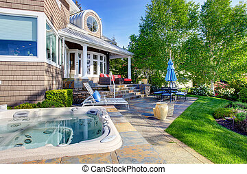 Luxury house exterior with impressive backyard design, patio area and hot tub.