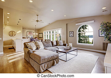 Cozy living room and dining room interior in beige tones with vaulted ceiling and hardwood floor.