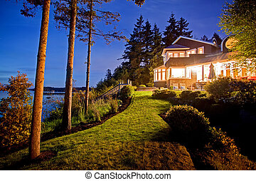 Large two story house with lots of lights in the summer evening.