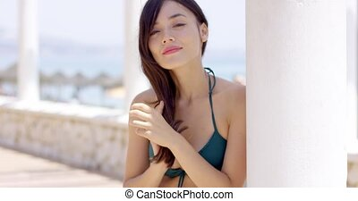 Young woman in a bikini standing daydreaming leaning up...