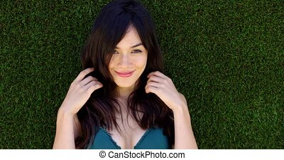 Pretty woman with long brown hair lays in grass while...