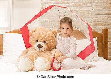 Little girl playing with toy bear - Portrait of expressive...