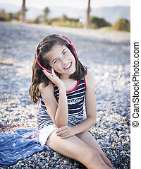 Cheerful little girl listening to music on headphones