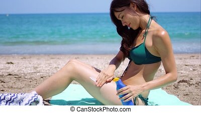 Young woman applying sun cream to her legs as she sits...