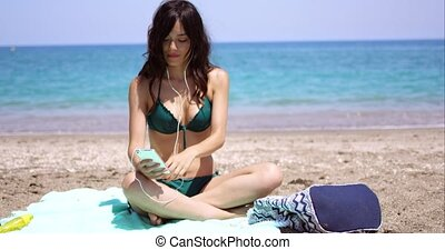 Young woman listening to music on a beach - Young woman...