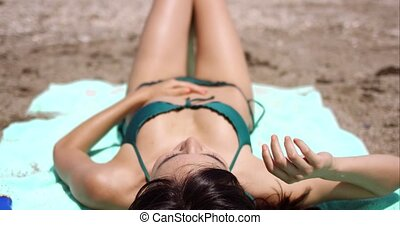 Woman suntanning on a tropical beach in summer sun - Woman...