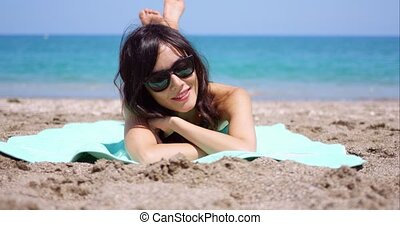 Pretty woman in sunglasses sunbathing on a beach lying on a...