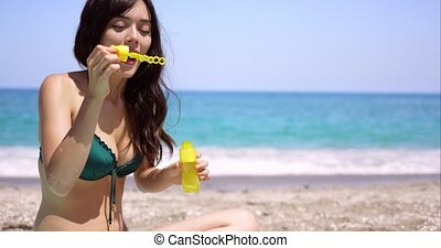 Fun young woman blowing bubbles on a beach as she sits in...