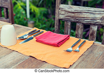 close up of cutlery with glass and napkin on table - table...