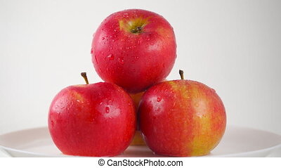 Girl hand taking one wet red apple, light background. 4K...