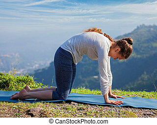 Sporty fit woman practices yoga asana Marjariasana outdoors...