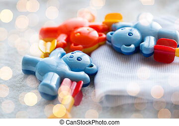 close up of baby rattle and clothes for newborn - babyhood,...