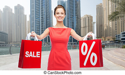 happy woman with shopping bags over dubai city - sale,...