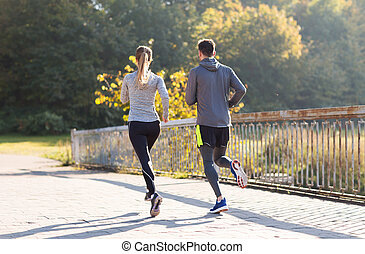 couple running or jogging outdoors - fitness, sport, people...