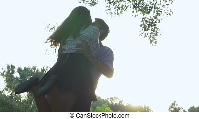 Romantic couple hugging and spinning in the park