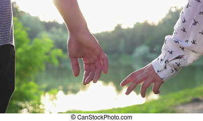 Close-up of couple holding hands at sunset and walking...