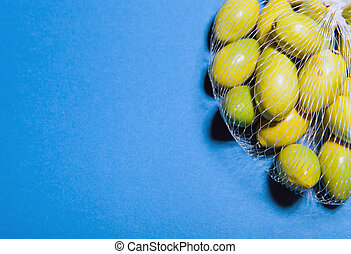 Green olives in the mesh bag, cooking concept