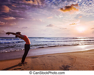 Young sporty fit woman doing yoga Sun salutation Surya...