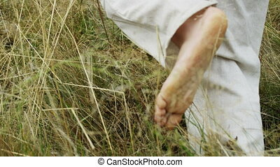 Young man runs on open air. Barefoot young man in white is...