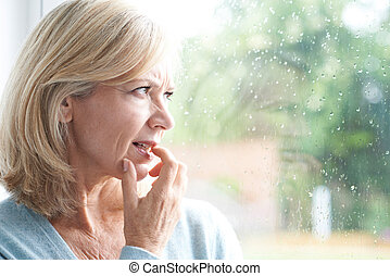 Sad Mature Woman Suffering From Agoraphobia Looking Out Of...