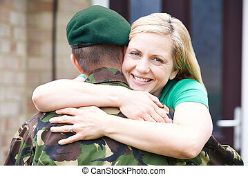 Portrait Of Wife Hugging Army Husband Home On Leave