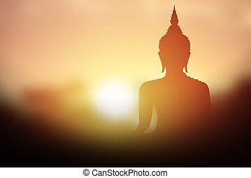 Silhouette of Buddha with sun shining from behind