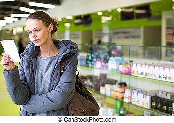 Young woman looking for the right pills in a modern pharmacy...