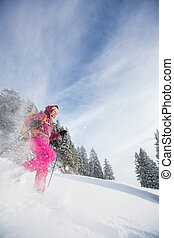 Young woman snowshoeing in high mountains