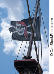 A skull and cross bones pirate flag waving in the wind