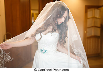 Morning of bride - Pretty bride puts on her wedding dress in...