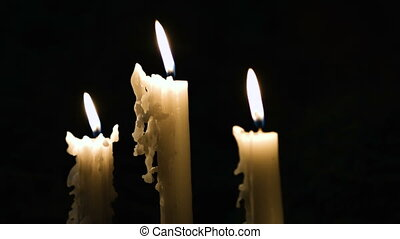 Three burning candles of differing size on a black...