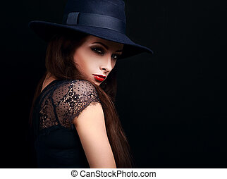 Beautiful expressive bright makeup female model with red hot lips posing in hat on black background