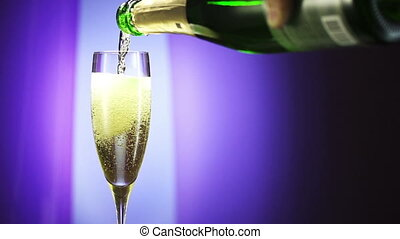 Bottle filling champagne flute against blue background slow...