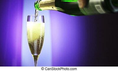 Bottle filling champagne flute against blue background. slow...